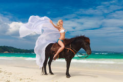 Happy girl walking with horse on a tropical beach Royalty Free Stock Images