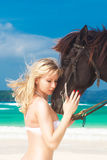 Happy girl walking with horse on a tropical beach Stock Photo