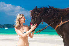 Happy girl walking with horse on a tropical beach Stock Image