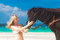 Happy girl walking with horse on a tropical beach Stock Photos