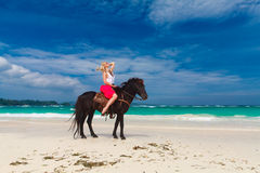 Happy girl walking with horse on a tropical beach Stock Images