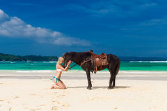 Happy girl walking with horse on a tropical beach Royalty Free Stock Photography