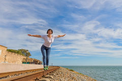 Happy girl walking on rails and smiling. Stock Photography