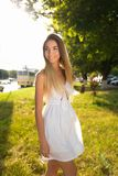 Happy girl walking in the summer in park. White dress long hair. Emotions of joy fun outdoor recreation. Concept walk