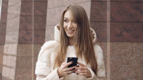 Happy girl walking, using the phone and smiling near the office. Slowly.  stock footage