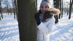 Happy girl walking in winter forest, backlit, happiness, young woman flirting, looking into camera, sun`s rays shine. Through trees, winter fun, woman in love stock video