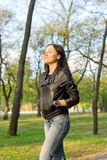 Happy girl walking through woodland. Happy casual young girl in jeans and a leather jacket walking through woodland with the sun in her face Royalty Free Stock Images