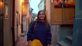 Happy girl walks along the narrow evening street of the old city, front view, portrait