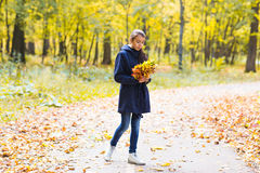 Happy girl  walks in autumn park with maple Stock Photo
