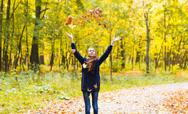 Happy girl  walks in autumn park throws up fallen Stock Photography