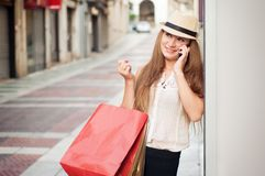 Happy girl walks through the street after shopping. She holding royalty free stock photos