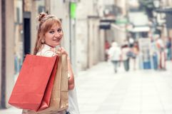 Happy girl walks through the street after shopping. She holding royalty free stock images