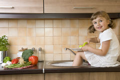 Happy girl washing dishes Royalty Free Stock Photo