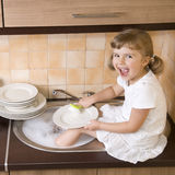 Happy girl washing dishes Stock Images