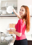 Happy girl washing plates in home kitchen Stock Image