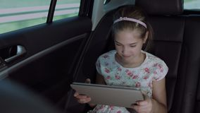 Happy girl watching cartoons on tablet in the car. Happy elementary age girl watching cartoons online on digital tablet in the back seat of the car during stock footage