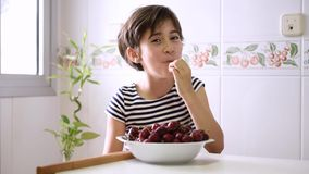 Happy girl watching and eating a big bowl of cherries. Happy girl watching and eating a big bowl of cherries in the kitchen at home stock video