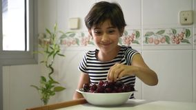 Happy girl watching and eating a big bowl of cherries. Happy girl watching and eating a big bowl of cherries in the kitchen at home stock footage