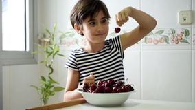 Happy girl watching and eating a big bowl of cherries. Happy girl watching and eating a big bowl of cherries in the kitchen at home stock video footage