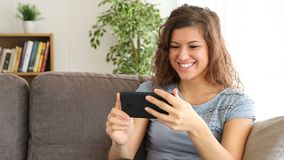 Girl watching media content in a smart phone at home stock video footage