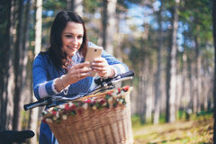 Happy girl watching media in a smart phone sitting in the street beside her bicycle Royalty Free Stock Images