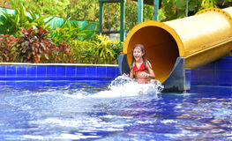 Happy girl  on water slide Royalty Free Stock Images
