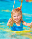 Happy girl on water swing Stock Images