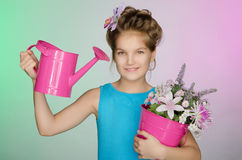 Happy girl with watering can and beautiful flowers Royalty Free Stock Photography