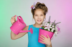 Happy girl with watering can and flowers Royalty Free Stock Images