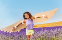 Happy girl waving cardboard wings like a bird. Portrait of happy preteen girl wearing costume of a bird, standing in lavender field and trying to fly Stock Photography