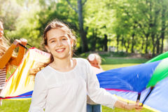 Happy girl waving colorful parachute with friends. Close-up portrait of happy Caucasian girl waving colorful parachute with her friends outdoor in spring Royalty Free Stock Photos