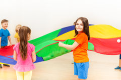 Happy girl waving colorful parachute with friends. Portrait of Caucasian dark-haired girl holding rainbow parachute and playing with friends in kindergarten Stock Photos