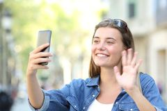Girl waving hand during a phone video call in the street. Happy girl waving hand greeting during a phone video call in the street Stock Images