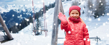 Happy girl waving hand over winter background Stock Image