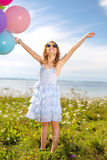Happy girl waving hands with colorful balloons Stock Images
