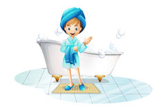 A happy girl wearing a blue robe and a blue shower cap Stock Photography