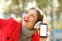 Girl listening to music and showing smartphone screen. Happy girl wearing red jacket and headphones listening to music and showing smartphone screen in a park in Royalty Free Stock Photos