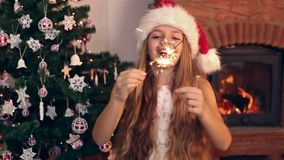 Happy girl wearing a santa hat laughing and waving with christmas sparklers stock footage