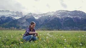 Happy girl weaves a wreath of yellow dandelion flowers sitting in meadow on mountains background. Slavic national. Traditions 4k stock video