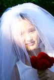 Happy girl in wedding dress. Portrait of smiling girl behind veil of traditional white wedding dress, holding red bouquet of flowers stock photo
