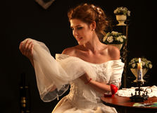 Happy girl in a wedding dress sits at table. Stock Photography