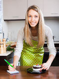 Happy girl   weighing cakes on kitchen scales Royalty Free Stock Photography