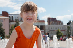 Happy girl in wet dress laughs near fountain in summer city. Happy girl in wet dress laughs near dry fountain in summer city at sunny day Royalty Free Stock Photography