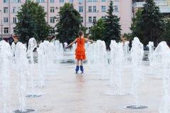 Happy girl in wet dress roller skates in fountain in summ. Happy little girl in wet dress roller skates in fountain in summer city, back view Royalty Free Stock Photos