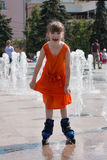 Happy girl in wet dress roller skates in fountain. In summer city Stock Image