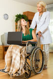 Happy girl in wheelchair  working on laptop Royalty Free Stock Photography