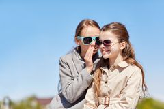 Happy girl whispering secret to her friends ear Stock Photo