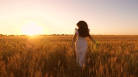 Happy girl in white dress with long developing hair running through a field with golden wheat at sunset. Slow motion.