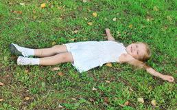 Happy girl in white lies on green grass in summer park Royalty Free Stock Photo