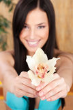 Happy girl with white orchid. Pretty smiled woman holding white orchid in bikini, focus on flower stock photography